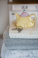 Pastel teapot on stack on woollen blankets