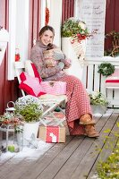 Young woman holding present and smiling on decorated veranda