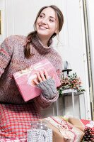 Young woman smiling and holding presents standing in front of door