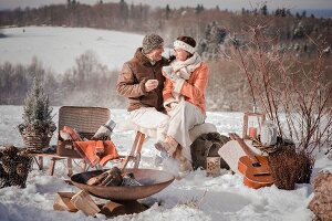 Man and woman enjoying a winter picnic in a snowy landscape