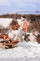 Man and woman with guitar during a winter picnic in a snowy landscape