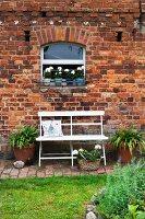 White bench in garden against brick façade