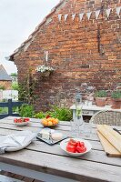 Set table on terrace adjoining brick wall