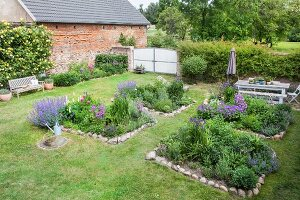 Beds edged with stones in summery cottage garden