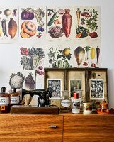 Botanical illustrations above collection of flea-market finds on top of cabinet