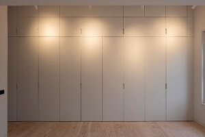 Floor-to-ceiling, minimalist fitted cupboards lit by spotlights