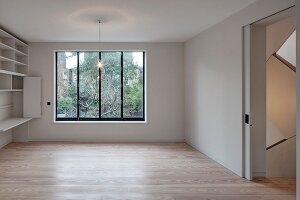 Empty minimalist interior with fitted cabinets, parquet floor and sliding door