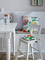 A white highchair with colourful cushion at a dining table and a bench with various cushions in a country house-style room