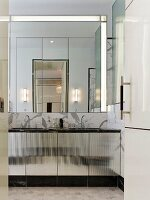 Twin sinks, marble cladding and mirrored wall in elegant bathroom