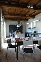 Modern, open-plan kitchen below rustic wood-beamed ceiling