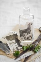 Still-life arrangement of vintage family photo and bottle decorated with vintage picture of goats