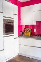 White, modern kitchen with hot pink walls