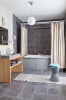 Grey tiles and bath with four-poster frame and shower curtains in bathroom