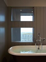 Water in free-standing bathtub below interior window in wood-clad wall