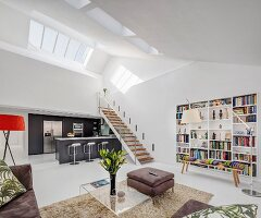 Gallery and skylights in open-plan interior of modern lift apartment with white walls