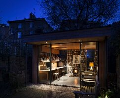 View into illuminated study with log burner and glass window
