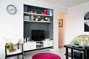 White shelves and TV on sideboard in grey-painted niche in living area