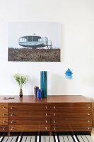Vases on retro sideboard, blue pendant lamp and photo with architectural motif
