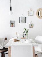 Gedeckter Frühstückstisch vor Wand mit verschiedenen aufgehängten DIY-Spiegeln