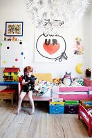 Girl wearing headphones sitting on bed in colourful bedroom