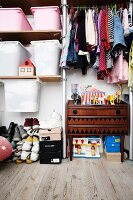 Clothing hung in open-fronted wardrobe above retro cabinet next to storage bins above stacked shoes