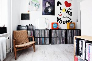 Worn retro armchair in front of record collection in black shelving modules in living area