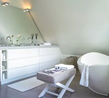 free-standing bathtub and upholstered stool in attic bathroom