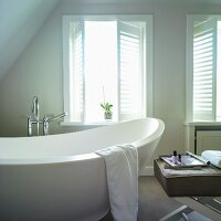 Free-standing bathtub in attic bathroom next to window with louvre shutters