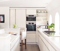 Bright, modern, country-house kitchen with open-fronted shelves and island counter