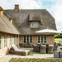 Wicker furniture on terrace outside brick house with thatched roof
