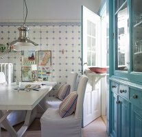 Dining area against traditional white and pale blue wall tiles in kitchen