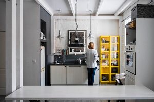 Woman cooking in modern white and grey kitchen standing next to bright yellow shelves
