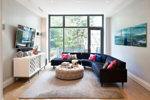 Large blue corner sofa and glass wall in elegant living room