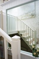 Reflection of staircase in wall-mounted mirror with white wooden frame