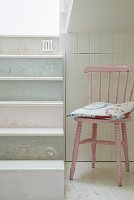 Pink-painted kitchen chair in niche next to staircase with steps painted in pastel shades