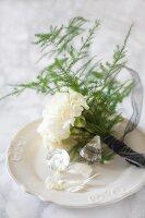 Nelkensträußchen mit Zierspargel und Kristallen auf Porzellanteller