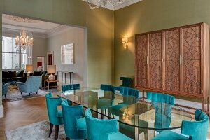 Oval glass table, petrol-blue upholstered chairs and modern cupboard in grand dining room with view into living room through wide, open doorway