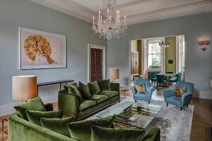Elegant green velvet sofa set, light blue armchairs and crystal chandelier hanging from stucco ceiling in grand living room