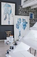 White wooden staircase, framed pictures and various pots of paint in artist's studio