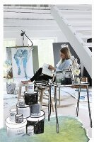 Outlines drawn on photo of painter at side table and pots of paint in artist's studio