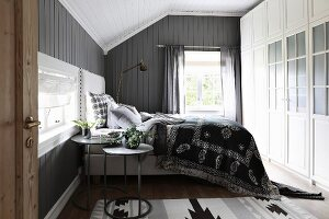 Box-spring bed in rustic bedroom with grey-painted wooden walls