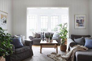 Armchairs in front of wide, open doorway and sofa in window bay in comfortable living room