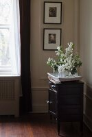Tray of white flowers on chest of drawers