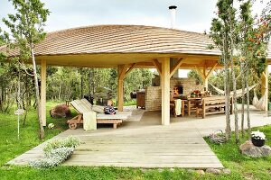 Comfortable sun loungers, dining area and pizza oven under large pavilion