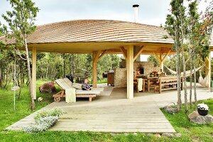 Großer Pavillon mit gemütlichen Sonnenliegen und Essplatz vor Pizzaofen