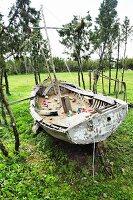 Rustikales Segelboot auf Wiese als Sandkasten