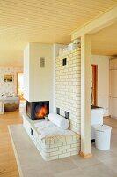 Gemütlicher Kaminplatz mit Ziegelwand-Raumteiler in offenem Wohnraum mit heller Holzdecke