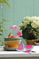 Hand-made, watermelon-slice invitation cards made from folded paper next to ceramic bowls on garden table