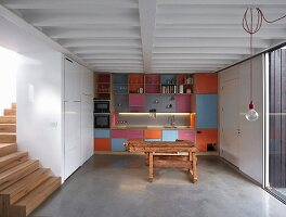 Colourful fitted kitchen, rustic workbench and white fitted cupboards