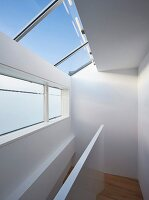 Modern stairwell with white balustrade, transom windows and skylights